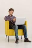 L'uomo che si siede in poltrona facendo uso del computer portatile Fotografie Stock