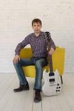 L'uomo che si siede in una sedia e che tiene una chitarra Immagini Stock Libere da Diritti