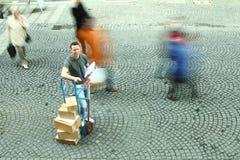 L'uomo che sta con Dolly Of Boxes While Crowd cammina vicino Fotografia Stock