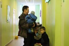 L'uomo che tengono un bambino ed i bambini stanno nella linea all'ospedale ricevono i benefici in un'ammissione aspettante dell'i fotografia stock libera da diritti
