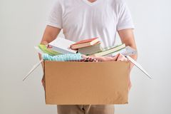 L'uomo che tengono un libro ed i vestiti donano la scatola Concetto di donazione fotografia stock