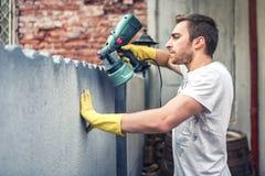 L'uomo che usando i guanti protettivi che dipingono una parete grigia con la pittura di spruzzo spara Giovane operaio che rinnova Fotografie Stock Libere da Diritti