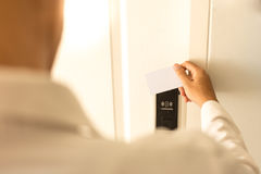 L'uomo che usando il keycard senza contatto per sblocca la porta in hotel Immagine Stock