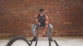 L'uomo chested nudo muscolare bello della palestra sta facendo l'esercizio della corda di battaglia Movimento lento archivi video