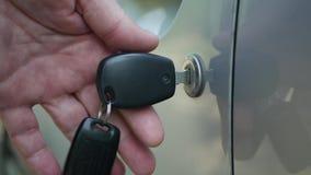 L'uomo chiude e blocca la porta del veicolo utilizzando il sistema meccanico e il tasto auto video d archivio