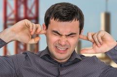 L'uomo chiude le orecchie con le dita per proteggere da rumore forte Fotografie Stock