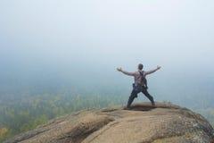 L'uomo in cima alla montagna gode della bellezza della natura per raggiungere gli obiettivi Immagine Stock