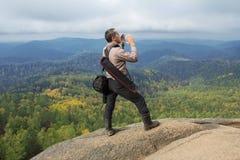 L'uomo in cima alla montagna gode della bellezza della natura per raggiungere gli obiettivi Fotografia Stock Libera da Diritti