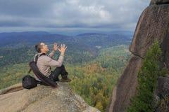 L'uomo in cima alla montagna gode della bellezza della natura per raggiungere gli obiettivi Fotografia Stock