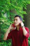 L'uomo cinese asiatico libero trascurato felice sta ascoltando musica e sta indossando un trasduttore auricolare fotografia stock libera da diritti