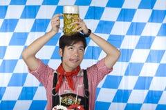 L'uomo cinese Lederhose tiene la testa dello stein della birra Immagini Stock