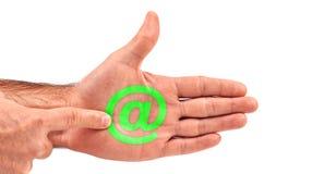 L'uomo clicca il email @ al bottone del segno sulla sua palma aperta Immagine Stock
