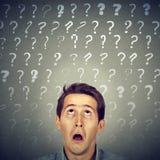L'uomo colpito curioso confuso non ha molte domande e risposta Fotografia Stock