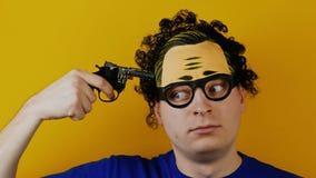 L'uomo comico con la rivoltella della pistola del giocattolo si spara nel divertimento di dirigere verso video d archivio
