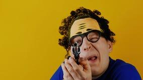L'uomo comico riccio con la rivoltella della pistola del giocattolo punta sulla macchina fotografica per divertimento archivi video
