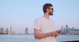 L'uomo compone il numero sul telefono ed i colloqui sui precedenti del panorama del Dubai Primo piano della mano video d archivio