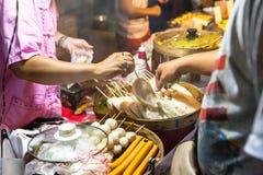 L'uomo compra l'alimento della via al mercato di domenica Fotografia Stock Libera da Diritti