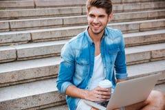 L'uomo con bere del computer portatile porta via il caffè sulla scala Fotografia Stock Libera da Diritti