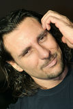 L'uomo con capelli lunghi graffia la sua testa Fotografia Stock