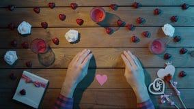 L'uomo con cuore di carta si siede dalla tavola di legno decorata, vista superiore stock footage