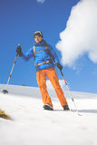 L'uomo con i pali di trekking passa attraverso la neve nelle montagne Fotografie Stock Libere da Diritti
