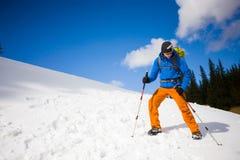L'uomo con i pali di trekking passa attraverso la neve nelle montagne Fotografia Stock