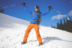 L'uomo con i pali di trekking passa attraverso la neve nelle montagne Immagine Stock
