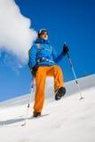 L'uomo con i pali di trekking passa attraverso la neve nelle montagne Fotografia Stock Libera da Diritti