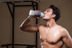 L'uomo con i supplementi degli elementi nutritivi nella palestra di sport Immagini Stock