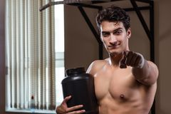 L'uomo con i supplementi degli elementi nutritivi nella palestra di sport Fotografie Stock