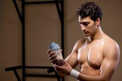 L'uomo con i supplementi degli elementi nutritivi nella palestra di sport Immagine Stock Libera da Diritti