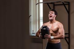 L'uomo con i supplementi degli elementi nutritivi nella palestra di sport Fotografie Stock Libere da Diritti
