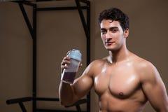 L'uomo con i supplementi degli elementi nutritivi nella palestra di sport Fotografia Stock Libera da Diritti