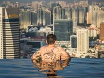 L'uomo con i tatuaggi esamina la città dallo stagno dell'infinito Fotografia Stock