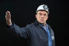 L'uomo con il minatore delle miniere di carbone Hat e l'abbigliamento della sicurezza indica Immagine Stock