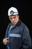 L'uomo con il minatore delle miniere di carbone Hat e l'abbigliamento della sicurezza indica Fotografia Stock