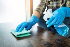 L'uomo con il panno che pulisce la tavola di legno nella casa usa lo straccio ed il liquido immagini stock libere da diritti