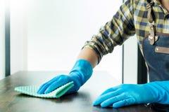 L'uomo con il panno che pulisce la tavola di legno nella casa usa lo straccio ed il liquido immagine stock libera da diritti