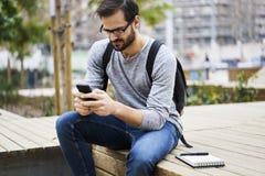 L'uomo con il telefono cellulare nelle reti sociali tramite smartphone si è collegato al wifi libero in città universitaria Immagini Stock Libere da Diritti