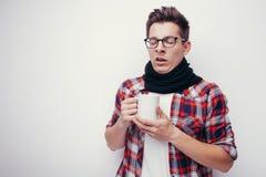 L'uomo con influenza e febbre ha avvolto giudicare la tazza di tè curativo isolata sopra bianco Immagini Stock Libere da Diritti