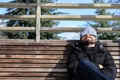 L'uomo con l'inverno copre, sedendosi su un banco di legno con neve immagini stock libere da diritti