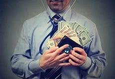 L'uomo con l'euro ed il dollaro incassano il suo portafoglio che controllano sulla sua situazione finanziaria Fotografia Stock