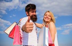 L'uomo con la barba mostra il pollice sul gesto Consiglio ora da comprare Clienti felici della famiglia Le coppie nell'amore racc fotografia stock