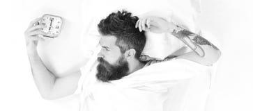 L'uomo con la barba si trova sugli strati ed il cuscino, aspetta immagine stock