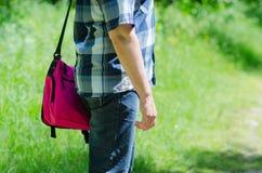 L'uomo con la borsa per il taccuino sulla spalla sta sul percorso Fotografia Stock Libera da Diritti