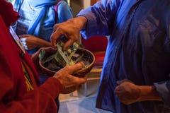 L'uomo con la camicia blu sta mettendo 25 dollari canadesi in un canestro fotografie stock libere da diritti