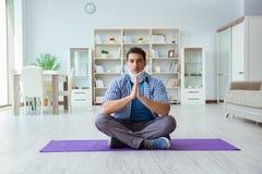 L'uomo con la lesione del collo che medita a casa su pavimento Fotografie Stock