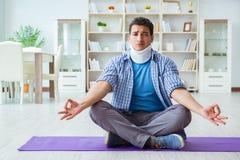 L'uomo con la lesione del collo che medita a casa su pavimento Fotografie Stock Libere da Diritti