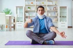 L'uomo con la lesione del collo che medita a casa su pavimento Fotografia Stock