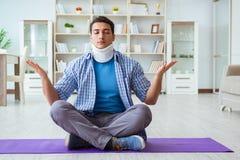 L'uomo con la lesione del collo che medita a casa su pavimento Immagine Stock